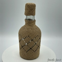 Small vintage bottle covered with raffia
